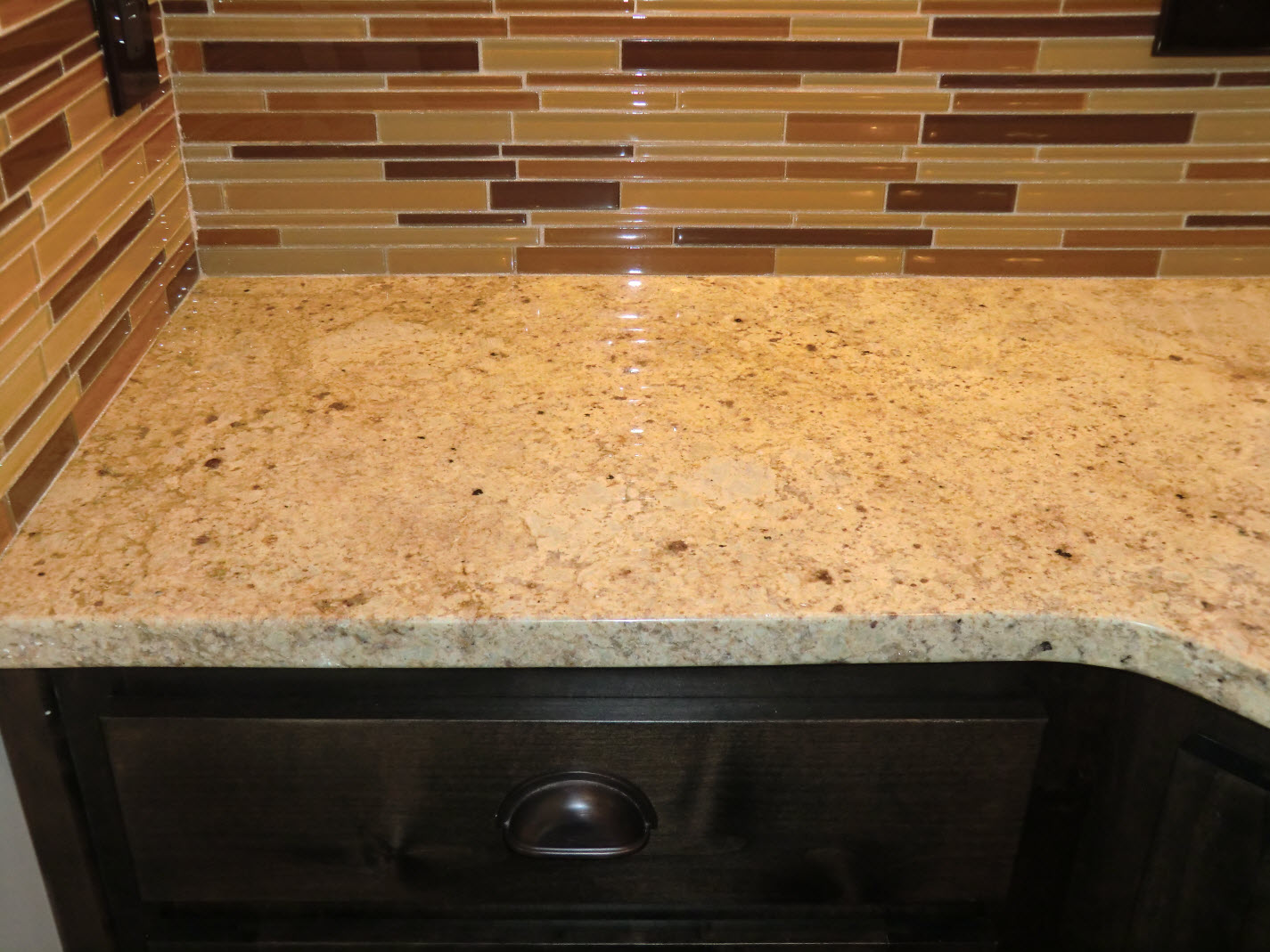 Close up of cabinet, countertop & glass tile backsplash, glowing
